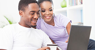Couple on laptop using debit card